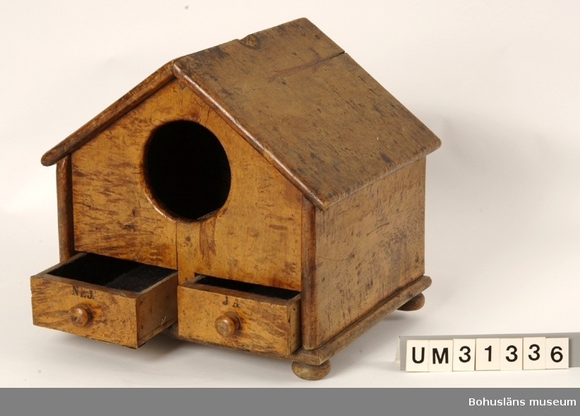 """Kvadratisk låda av masurbjörk med sadeltak, rund öppning med två utdtragbara lådor på ena kortsidan samt kulfötter. Inuti lådan en skiljevägg mellan de små lådorna. Mitt på  taket ett runt hål  för en del som fattas. Lådorna är brännmärkta med texten """"NEJ"""" respektive """"JA"""". Lådorna är invändigt klädda med svart filt. I ena lådan ligger fyra bruna träkulor, i den andra  två. """"Toppen"""" , toppdelen, skall enligt uppgift från givaren finnas i ägo hos någon i familjen Macfie-Thorburn. Lådan användes då nya medlemmar skulle röstas in i Bohuslänska Curlingklubben.  Ur Nationalencyklopedin, NE.se: Ballotering Ballotering (av fr. ballotte 'liten boll', 'liten kula', diminutiv av balle 'boll'), sluten omröstning. Ordet avsåg ursprungligen omröstning med kulor som symboler för avgivna röster, vita för ja och svarta för nej; detta tillvägagångssätt används främst i vissa illustra föreningar i samband med inval av nya medlemmar.  Balloteringslådan ingår i en gåva från Bohuslänska curlingklubben, BCK genom Bengt  Hansson. Klubben har idag inga möjligheter att förvara äldre föreningsmaterial. Sedan 2007 står man utan """"istid"""", träningstid i hallen i Uddevalla efter det att ishockeyn tilldelats denna. Därför kan man inte bedriva någon verksamhet f. n. (2008). En del av föremålen i den aktuella gåvan har tidigare förvarats i Sportstugan vid Bjursjön som BCK byggde tillsammans med några andra föreningar 1933. Här var BCK andelsägare och disponerade ett eget rum.  Se Bilagepärmen UM31336 för kopia av artikel Bohuslänska Curlingklubben1852 - 2002 av Gunnar Klasson samt UM4661 med artiklar om BCK och om curlingstenar.  Se också arkivmaterial och föremål från BCK som  skänktes till Uddevalla museum 1950 respektive 1975  och som förvaras i Bohusläns Föreningsarkiv; UM5352, UM75.3.1 - UM75.3.2, UM75.3.5 - UM75.3.6 s och enligt katalogen överförts dit 16/11 2000.  Litt: Bohus-Posten 1947. Artikel om Bohuslänska Curlingklubben.  Olsson, Hugo: Uddevalla, en bildbok,  Bohusläns museums förlag. Ud"""
