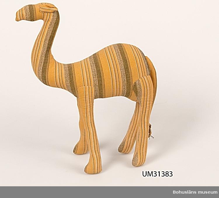 Kramdjur i form av långsmal kamel med svans. Sytt av gul- och brunrandigt bomullstyg, hårt stoppad med mjukt material, kanske kapock eller ull. Handsytt. Några år före bildadet av Föreningen Bohus Stickning 1939 sökte föreningens initiativtagare efter lämplig produktion, passande för hemtillverkning. 1937 provade man tillverkning av julprydnader av glanspapper och förguyllda sädesstrån, senare sömnad av tygdjur och tydockor. Tygdjuret bör alltså vara tillverkade någon gång mellan åren 1937 och 1939. De modeller som tillverkades kunde vara hund, lejon, giraff, gris, kamel. Dessa djur fanns också till försäljning i Bohusslöjds butik i Göteborg. Det är dock oklart om tillverkning och försäljning av Vera Bjurströms djur övertogs av Bohusslöjd när Bohus Stickning bildades 1939 och hur länge de fanns i Bohusslöjds sortiment eller om djuren fanns inom båda företag samtidigt.  Givaren är sondotter till Vera Bjurström, en av Bohus Sticknings formgivare. Hon och syskonen hade flera olika djur och djuren i denna gåva är de som återstår.  Litt: Häglund, U. med bidrag av Ingrid Mesterton. Bohus Stickning. Bohusläns museums förlag 1999. Bohusslöjd. 100 år av hjärtans lust. Red. Monika Hallén. Bohusslöjd/Konstfliten Göteborg. 2006.