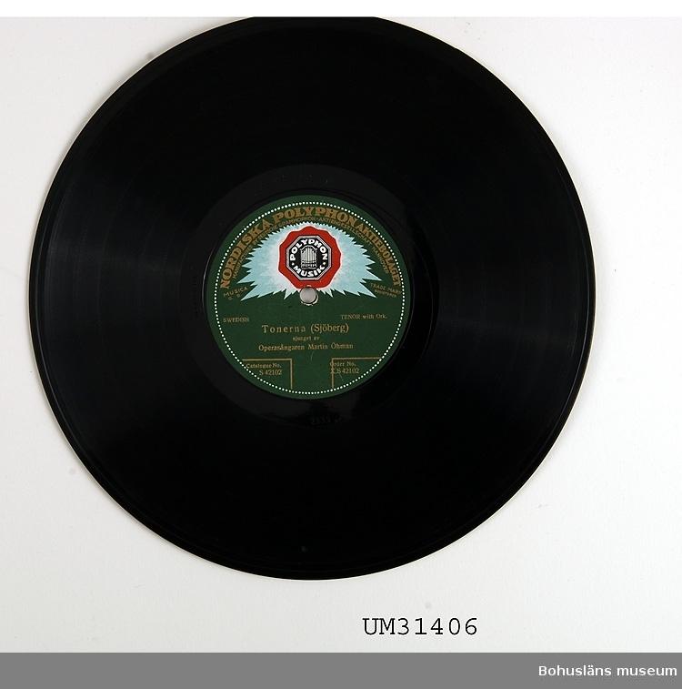 Grammofonskiva, stenkaka i papperfodral.  Ena sidan: Tonerna. Sjöberg. Operasångaren Martin Öman.  Andra sidan: Jungfrun under lind. W. Peterson-Berger. Operasångaren Martin Öman.   Skivmärke: Nordiska Polyphoneaktiebolaget  Grammofonskivan som ingår i skivsamling som spelats i en sommarstuga i Sundsandvik, byggd 1939. Skivorna spelades på en svart resegrammofon, se motsvarande modell UM026268. För ytterligare upplysningar om förvärvet, se UM31385.