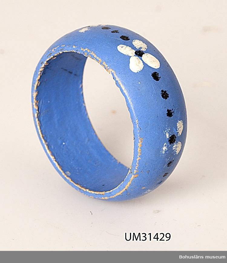 Svarvad servetthållare av målat trä, blå.  Föremålet har använts av familjen Abrahamson i deras sommarstuga i Sundsandvik, byggd 1939. För ytterligare upplysningar om förvärvet, se UM031385.