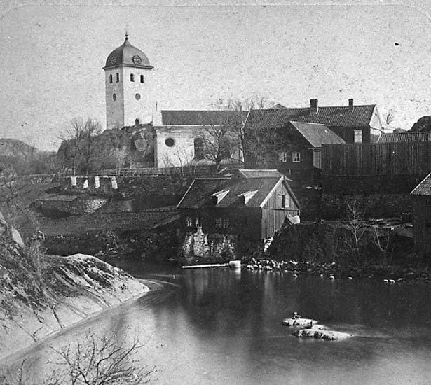 """Enligt text på fotot: """"Kyrkan och gamla Uddgrenska fastigheten vid Bäveån från sydväst""""."""