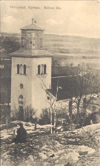 """Tryckt text på kortet: """"Herrestad. Kyrkan. Bohuslän"""". """"FÖRLAG: POSTEN, LANE, HERRESTAD"""". """"29 AUG. 1955""""."""