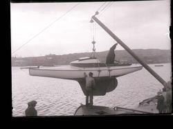 En segelbåt sjösätts på Grötö våren 1909. Lysekil i bakgrund