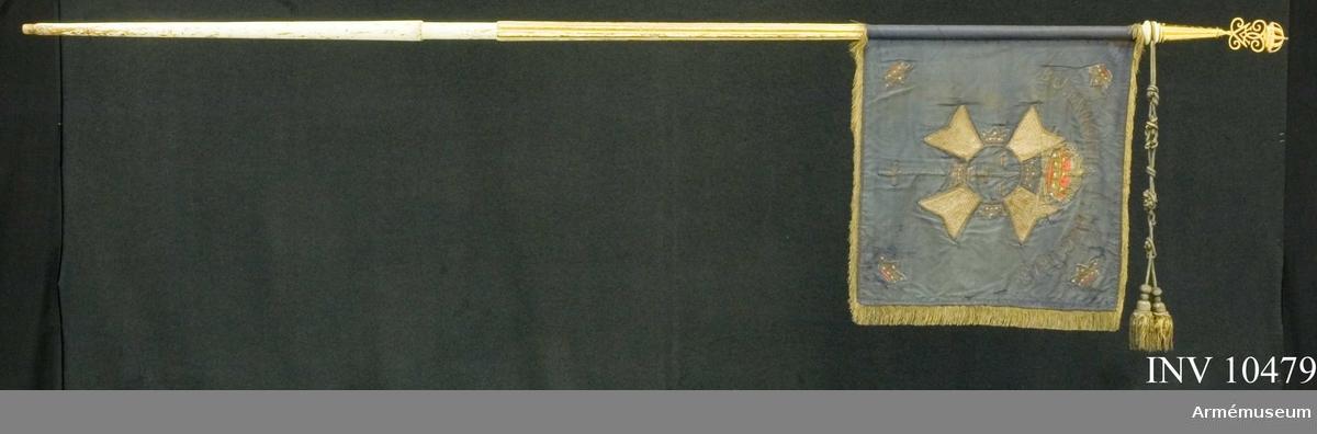 """Grupp B I.  Standaret är blått med guldfrans och guldkordong. Spets G V graverad på spetsskaftet: """"Gifvit till Mörnerska Hussar Regementet för visad Tapperhet den 7de December 1813 vid Bornhöft i Hollstein"""". Spetsens längd 160 mm och bredd 77 mm."""