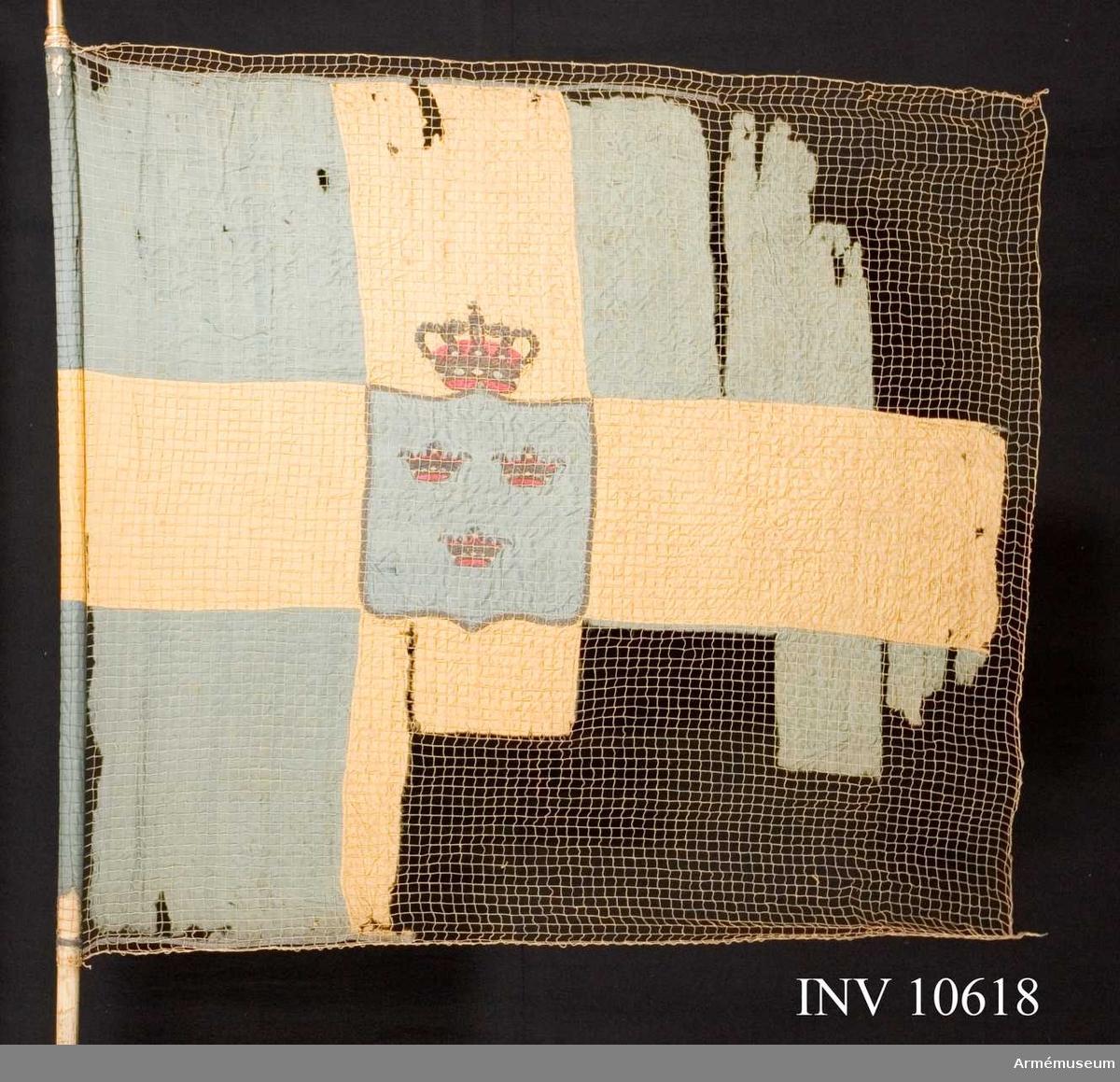 """Grupp B.  Duken blå och gul med vapnet """"tre kronor"""" i mittenfältet. Stång, holk och kravatt tillhör denna fana."""