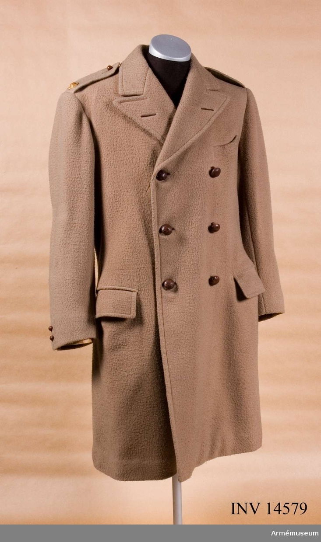 """Grupp C I. Överrock m/1918,- för officer. England. Överrock av beigefärgat kläde,tvåradig (med 3 knappar i varje). På sidan - 2 st fickor, 17 cm breda, försedda med fyrkantiga lock. På vänstra sidan i övre delen finns en ficka. Baktill: en slits 43 cm lång. Axelklaffar av samma kläde, 5 cm breda, 15 cm långa och fastsydda vid ärmsömmarna samt fästa vid överrocken med knappar av mindre format. På varje axelklaff stjärna - kännetecken för second leutant rang, stjärnan av gulmetall med röd emaljerad ring och påskrift: """"Tria Junita in uno"""".  Foder av tjockt beige yllefoder. På höger sida finns en innerficka med påsydd papperslapp: Firma namn: """"Andersson & Skeppard 13 Saloile Row, London, W Date: April 22. 1918"""", förnamn oläsligt, tillnamn """"Wikland"""". Knappar 6 st på framsidan av läder, 2,5 cm i diameter. På axelklaffarna knappar av mindre format, 1,3 cm i diameter. Krage liggande, öppen. Under kragen finns två benknappar för att knäppa till sleifen som är fastsydd till kragen."""
