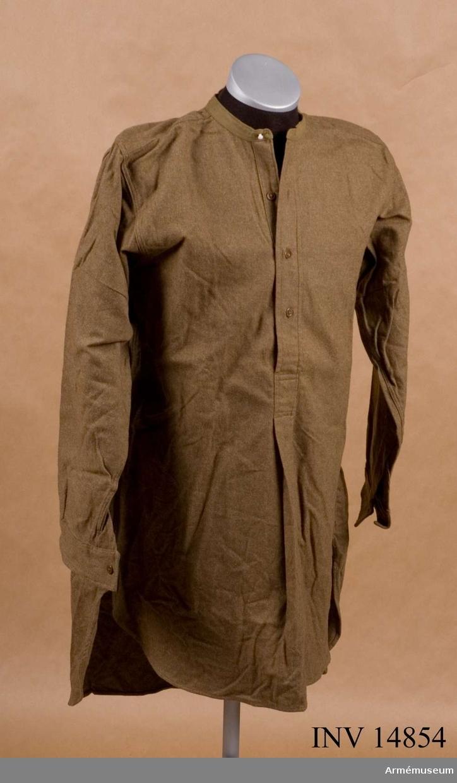 """Grupp C I. Skjorta, brun, England. Dep från K.A.I.D. modellkammare. Skjorta av mörkt khakifärgat ylletyg, som knäppes vid bröstet med tre khakifärgade benknappar. Krage saknas. På ryggen, vid halsöppningen finns det en firmaetikett med påskriften: """"15 Hawkes & Co Ltd  1 Savile Row. W.24 te Common Woolwich S.F. """"68. High St Camberley"""". Litteratur: Taschenbuch Brittisches Heer 1944. Felduniformen des Britischen Heeres. Tafel 1: bilder av khakifärgade uniformer.Enligt kapten W. Granberg"""