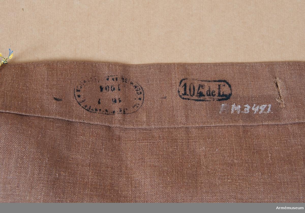 """Grupp C I.  Mattornister nr 1. Ur uniform m/1913 för manskap vid franska infanteriet. Av brun lärft med lock som stänges med 2 knappar av järn med påskrift """""""". På lockets baksida finns stämplar: 1) halvrund. Oläslig med datum """"16.1.1904"""", 2) """"104e de L"""" (Etthundrafjärde linjeinfanteriregementet).   Gehäng av bomullsband med spännen av metall."""