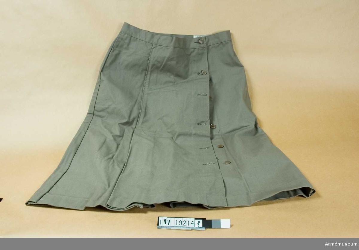 """Kjol m/1942. Storlek 46. Av gråbrungrönt bomullstyg. Omlottlagd med knäppning i vänster sida med en ficka på insidan som knäpps samtidigt med knapp tre. Linning i midjan. Veck fram och ett motveck mitt bak. På linningens avigsida en etikett med text: """"Tvättningsföreskrift. För att färgen ej skall blekas får denna uniform endast tvättas i varmt såpvatten. En mindre tillsats av soda är tillåten. Undvik skrubbning med borste samt frätande eller klorhaltiga tvättmedel"""". Har tillhört mobiliseringsutrustningen vid museet för konservator Gun Alder."""