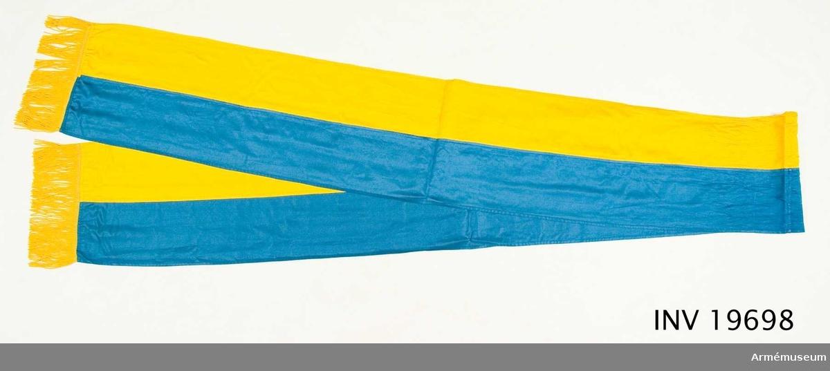 Kravatten är i gult och blått och har frans nedtill i guldfärg.  Samhörande nr AM 19697-99, fana, spets, kravatt, fodral.