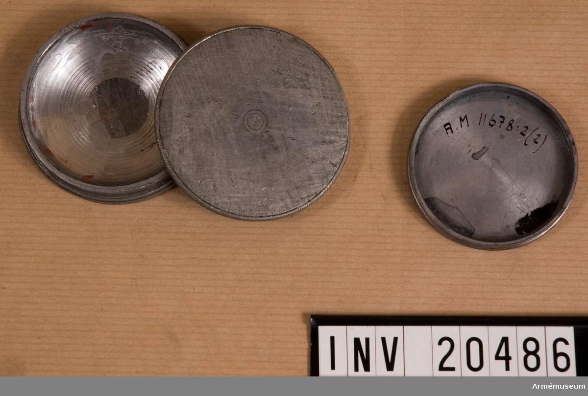 Grupp C I. Fodral med rött glas som är trasigt och smutsigt av svart färg.  Fodralet och dess lock är av någon vit metall. (Inv.förteckning:  tenndosor, 2 st). Den geleografiska apparaten, som användes för signalering,  infördes i ryska armén före världskriget 1914-1918 och var i  bruk under kriget. Apparaten har två glas, ett vitt och ett  rött.