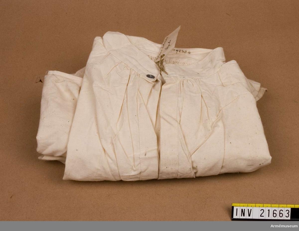 Samhörande gåva: 21660-4, skjortor. Grupp C I. Av lärft med fast upprättstående krage och långa ärmar.