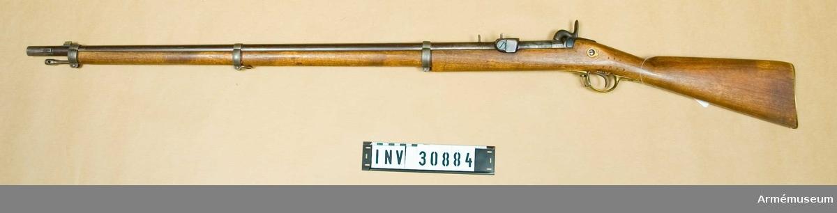 Samhörande nr 30884-5, gevär, bajonett. Bakladdningsgevär försök från bakladdningsgevär m/1864 Grupp E II.  Neg nr B 24, E 71/431. Antal räfflor: 6 st. Räffelstigning 1 varv på 112,8 cm. Loppets rel. längd 71 kal.Geväret är ursprungligen ett kammarladdningsgevär m/1864 (se AM 4428). Det är endast hanen och kammarstycket, som ändrats, varjämte pipan försetts med en särskild utdragningsinrätning. Vapnet är avsett för en med kopparhylsa försedd kantantändningspatron av samma typ som patroner m/1867.Pipan är brungjord. Kring patronlägets bakände finns utfräsning för patronflänsen. Längst bak på pipans översida finns en 4,7 cm lång och 0,7 cm bred ränna, som baktill går under piprännans till pipans bakände. I denna ränna är en regel eller en skena inpassad, vilken längst fram har ett litet framåtböjt, 1,3 cm långt handtag och baktill en nedåtriktad klack, som är inpassad i en urtagning i pipans bakplan. Klacken har baktill en urfilning för patronflänsen. Baktill på pipans vänstra sida finns anbringat 113 och på undersidan TLN, P, 152 och 1865.Urborrningen på det till slutstycke ändrade kammarstycket är utfylld. Nedtill är slustyckets främre kant avfilad. Tändstiftet sitter till höger samt består av två delar. Den bakre delen består av en 2,2 cm lång stålcylinder med 0,6 diam., vilken är anbringad i snäckan på knallhattstappens plats. Det för denna cylinder avsedda hålet går snett nedåt och litet framåt. En från höger i snäckan insatt skruv går i en urtagning baktill på cylinderns mitt och hindra nnan fortsätter så att säga i tunnelform under högra sidan av slutstyckets framdel samt går ut på den högra sidan av munstycket. I denna ränna är tändstiftets främre del, en baktill snett avskuren skena, anbringad. Omkring 2,8 cm bakom framänden blir skenan tunnare så att den kan gå i tunneln under slutstyckets framdel. Hela tändstiften kan röra sig omkring 5 mm bakåt och framåt. Framänden på tändstiftet bildar en 6 mm bred och 1 mm tjock, svagt avrundad, mejselliknande slagyta. 