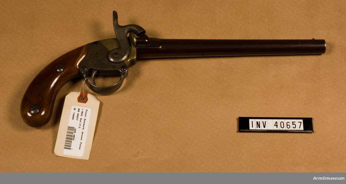 """Grupp E III. Pipan är brunerad och har ej framstock. Låsblecken är hälften järn och hälfen mässing. På låsblecket står """"N. S Jessen inventor Kiöbenhavn. Patent. 1862."""" Samtliga skruvar numrerade från 1 till 5."""
