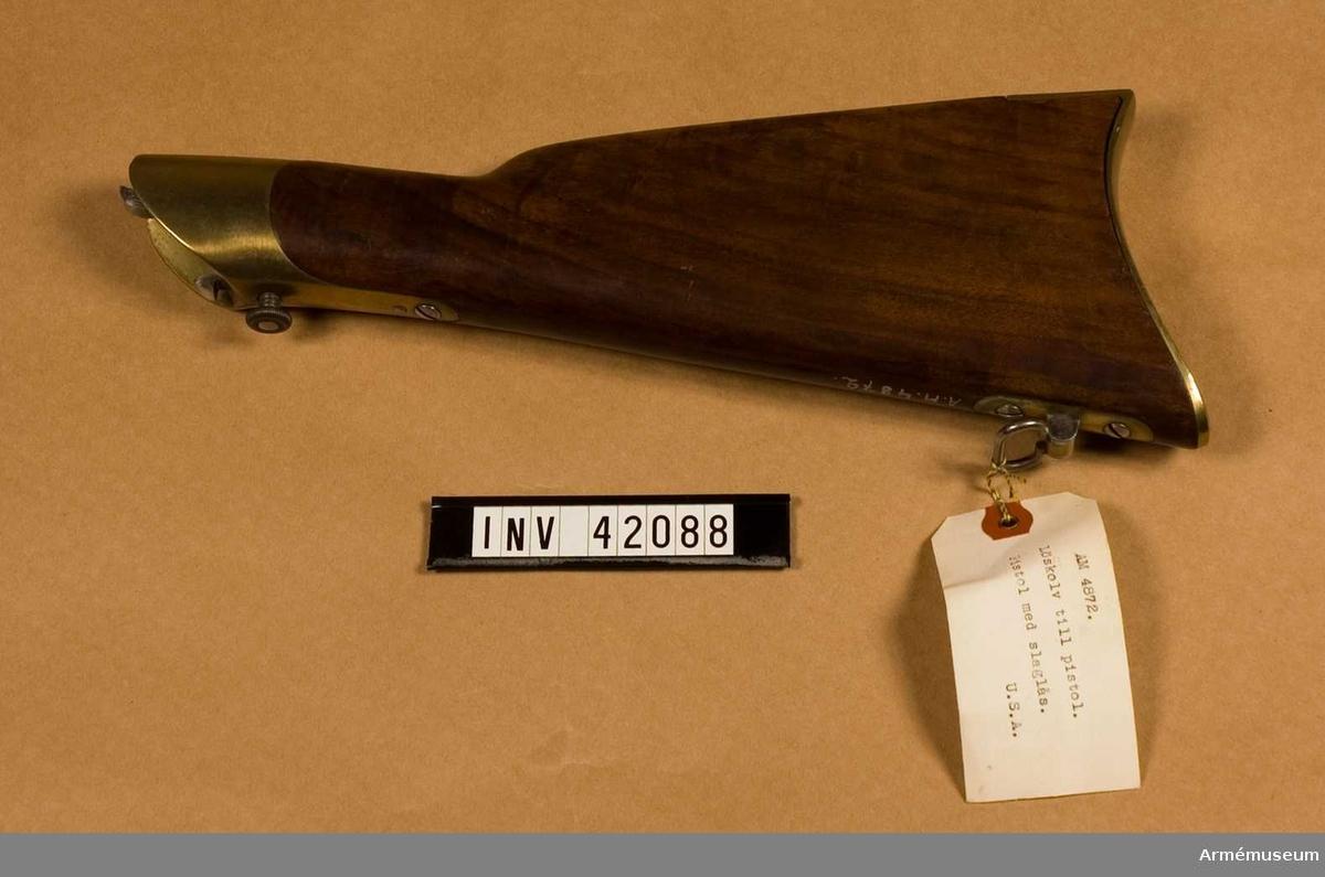 Grupp E III. Löskolven är av valnöt. Bakplåten är av mässing och en ganska kort, framtill tvärt avskuren flik, som skjuter in över kolvryggen. En skruv går genom fliken, en annan nedtill genom bakplåten. Löskolvens framände betäcks av ett kraftigt mässingsbeslag, vilket tjänstgör som häftjärn. I den urtagna del, som skall ligga an mot pistolkolvens baksida, finns upptill en häfthake, nedtill en spärrhake, bägge av stål, den sistnämnde på fjädrande skaft. Spärrhaken utlöses genom att man trycker in en på mässingsbeslagets undersida sittande tryckknapp. På kolvens underkant finns en rembygel, som sitter på en mässingsfot, vilken fasthålls av två skruvar. Beskrivning nedtecknad av J. Alm.