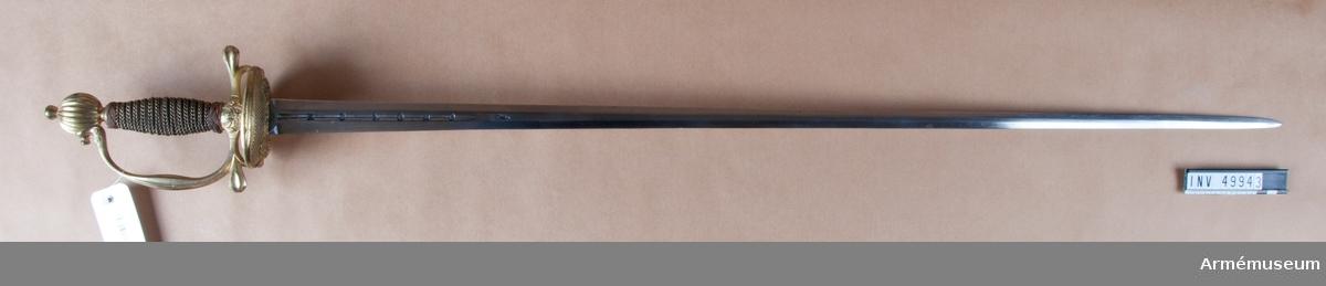 """Grupp D II.  Till museet genom byte. Klingan är tveeggad med flata åsar och har upptill på var sida en ungefär 160 mm lång blodrand. Vid vardera blodrandens slut finns på klingan en stämpel lika den på AM 49931 (pilspetsliknande). Fästet är ett """"franskt fäste"""" tillverkat av förgylld mässing. Knappen är svagt oval samt prydd med räfflor och har på översidan nitknapp, nedtill rätt kort hals. Kaveln har upp och nedtill en platt, 9 mm bred, flätning av försilvrad mässingstråd och är i övrigt lindad med två grova och två smala trådar av försilvrad mässingstråd, alla sammansnodda av två parter. Den ena smala och den ena grova tråden är högersnodda, de andra vänstersnodda. Parerplåten har ciselerade ornament längs mitten och pryds i övrigt av korsformiga, fina hål. Parerstångens armar blir  tjockare mot ändarna och är där, liksom handbygeln på mitten, prydda med räfflor. Klingan kan vara äldre än fästet. Utställningsetikett: Värja 1700-talets mitt för infanteriofficer."""