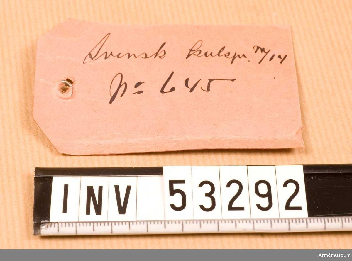 """Grupp E V. Använd vid laddning i svensk kulspruta m/1914.  Etikett med texten: """"Svensk kulspr m/14 No 645"""" Skarp patron."""