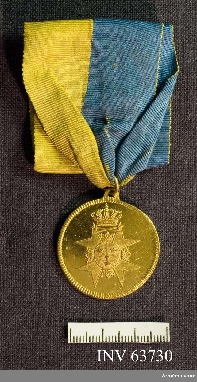 Grupp M II.  Åtsidan: Utan inskrift. Svärdsordens riddarstjärna under Kungl krona.    Frånsidan: Inskription inom en lagerkrans, på vilken äro fästade sex antika skeppsstävar (corona navalis). Medaljens båda ytterkanter strierade.
