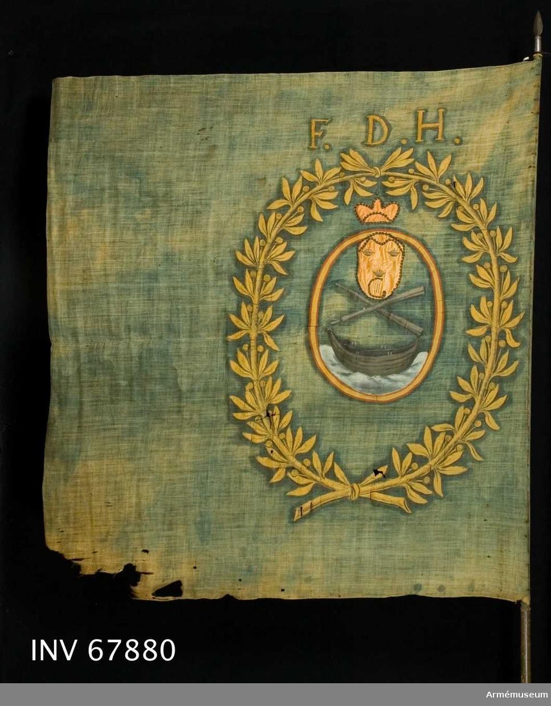 Duk av enkel blå linnelärft. Sydd av två horisontella våder.   Dekor:  Målad omvänt lika på båda sidor, en oval röd och guldkantad sköld, med en båt på ett böljande vatten och över båten två korsade åror. Skölden omges av en krans avt vå lagerkvistar nedtill och upptill hopknutna med blad och bär i gult. På skölden påsytt ett litet ovalt fält i orange atlas med kanter av guldspets, på fältet tre kronor och G III:s namnchiffer - ett G vari III allt i guld.  Över skölden men innanför kransen en sluten (?) krona i atlas. I överkanten, ovanför kransen F.D.H.  Duken fäst med järnspik på en smal skinnremsa.