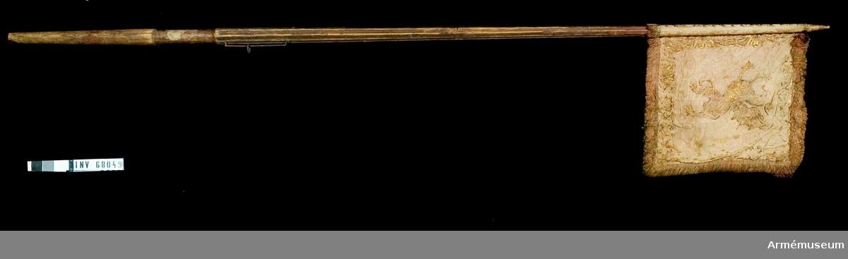 Duk: Tillverkad av dubbel röd sidendamast (mycket blekt). Mönster på damasten: Franska liljan ingår. Höjd på mönstret ej mätbar. Fäst med tre rader tennlickor utan band.  Dekor: Målad på dukens insida en gyllene grip (drake) - Östergötlands sköldemärke, med kontur i rödbrunt. Längs kanten en bård i guld av stiliserade bladverk, kronor av palmkvistar.  På dukens utsida Karl XI:s namnchiffer, dubbelt C under stor, sluten krona med kvistar i rött och grönt. Namnchiffret och kronan i guld med kontur i rödbrunt. Längs kanten bård lik insidans.   Frans: Dubbel i rött silke med guld.   Stång: Tillverkad av trä, rödmålad. Löpande bärring. Järnbeslag.   Saknar holk och spets.