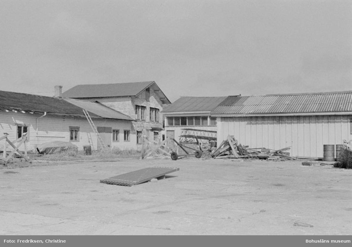"""Motivbeskrivning: """"Maleperts Båtvarv, Koön. Till höger i bild syns en f.d bensinstation (se Bb 18:10), där bakom en verkstad uppförd 1963. Till vänster i bild ett sillsalteri från 1800-taletets slut, vilket numera används till vinterförvaring av båtar (i byggnaden byggdes båtar under 1960 och 1970-talen). Datum: 19800722 Riktning: Nö"""