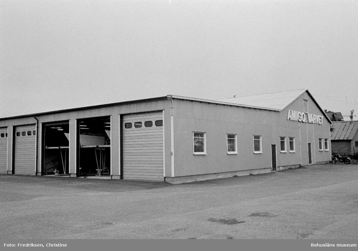 """Motivbeskrivning: """"Amigovarvet, Öckerö. Del av verkstadsbyggnad belägen längst bort i bild uppförd 1969, den främre delen uppförd 1977 (se även Bb 18:29)."""" Datum: 19800902 Riktning: S"""