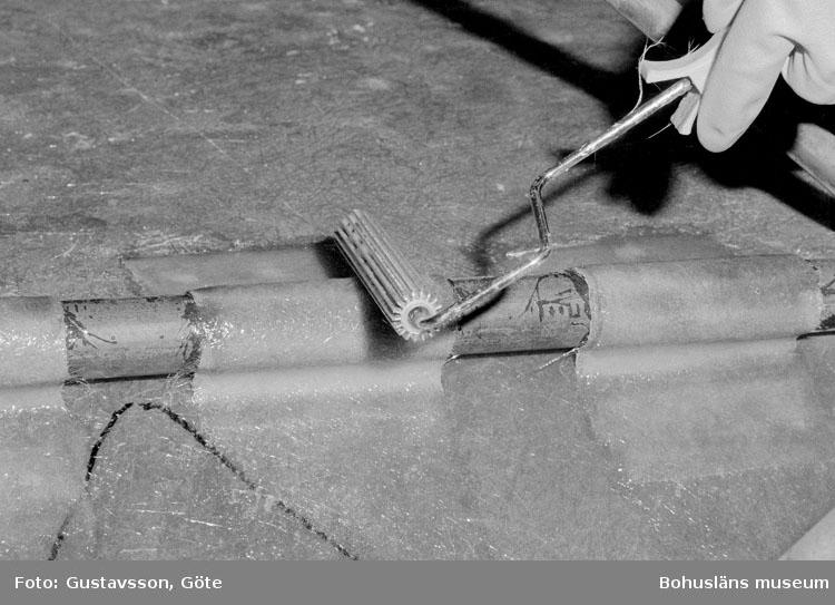 """Motivbeskrivning: """"Gullmarsvarvet AB, Ulseröd, Lysekil. Bild från sprutrummet nr 6.  På bilden syns en stålrulle som används till att glasfiberremsa med plast på skrovstativ."""" Datum: 19801031"""