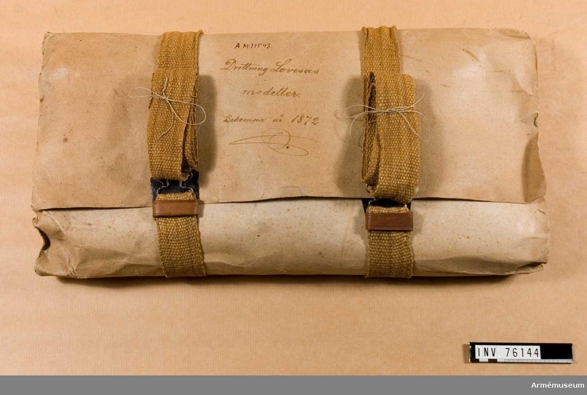 """Grupp I:II.  Paket med förbandsartiklar omslaget med grått lumppapper ihophållet av två sadelgjordsband,4,5 cm x144cm. med metallspännen och med en bärrem av läder, 30 cm. Innehåll: 4 st vita yllelindor 25 fot långa, ca 8 cm breda. 2 st vita linnelindor 25     """"        """",  9 cm  """". 2 st   """"       """"           25     """"        """",  8 cm, 8,5 cm b. 2 st   """"       """"           20     """"        """",  6 cm breda. 2 st   """"        """"         T20     """"        """", 6,5 cm   """" 2 st   """"        """"          20     """"         """",6,5 cm, 7 cm 4 st   """"        """"          10     """"         """", 5 cm 4 st hopbuntade, bruna bomullsband, 1 cm breda 2 st bomullslappar, 31 x 31 cm 2 st linnelappar, 31 x 31 cm 3 st   """"             , 50 x 50 cm 1 st bomullslapp, 48 x 49 cm 1 st bleckplåtstub, D 4 cm, 17, 5 cm lång innehållande linoljeindränkt linnelapp, s.k. oljeduk, 17 x 88 cm. 1 st oljeduk, 66 x 88cm. 1 st kuvert med fnöske (att lägga på sår) 1 st av linneduk (i dräll), 74 x 129cm 2 st linnelappar, 90 x 90 cm 1 st knappnålsbrev från Gusum i Söderköping 1 st kuvert med Charpie (=Charpi av franska Charpie, av lat. ca´rpere= plocka,=linneskav, söndeplockat linne, som förr mycket användes till förbindning av sår och särskilt i stora massor tillverkades för sjukvården i fält. (Nordisk Familjebok) 1 st paket med texten: Charpie, engelsk och rutig, innehållande linnelapp med genombrutet rutmönster, ca 16 x 16 cm samt lapp i tuskaftväv, (av fetvadd?) laminerad med fetvadd ca 37 x 60 cm. 1 bunt Charpie samt ett stycke fetvadd. Text på gråpappersomslaget: Drottning Lovisas modeller. Bekomna år 1872."""