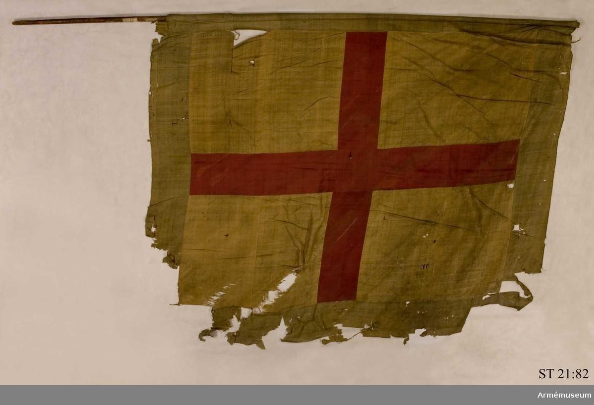 Duk av gult siden med grön bård. Mitt över duken ett rött kors. Den ursprungliga strumpan för stången är borta och därför har duken fästs direkt på stången. På stången finns en pappersetikett med information om att fanan skulle vara tagen i Narva 1700.