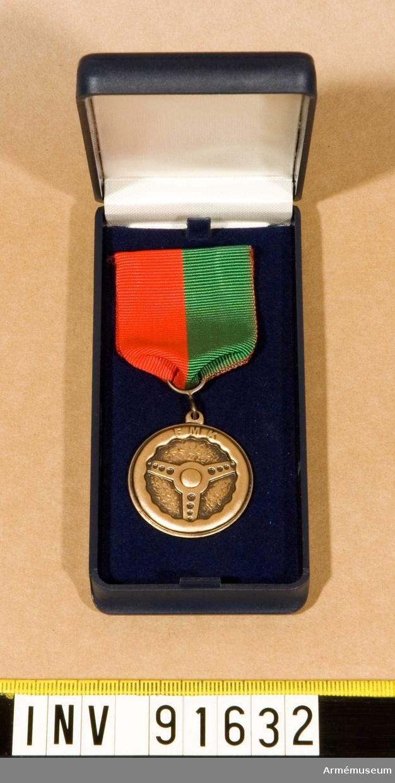 Etui innehållande Medalj.  FMKGM/SM. På framsidan en ratt och text. Text även på baksidan. Band till hälften grönt och till hälften rött.