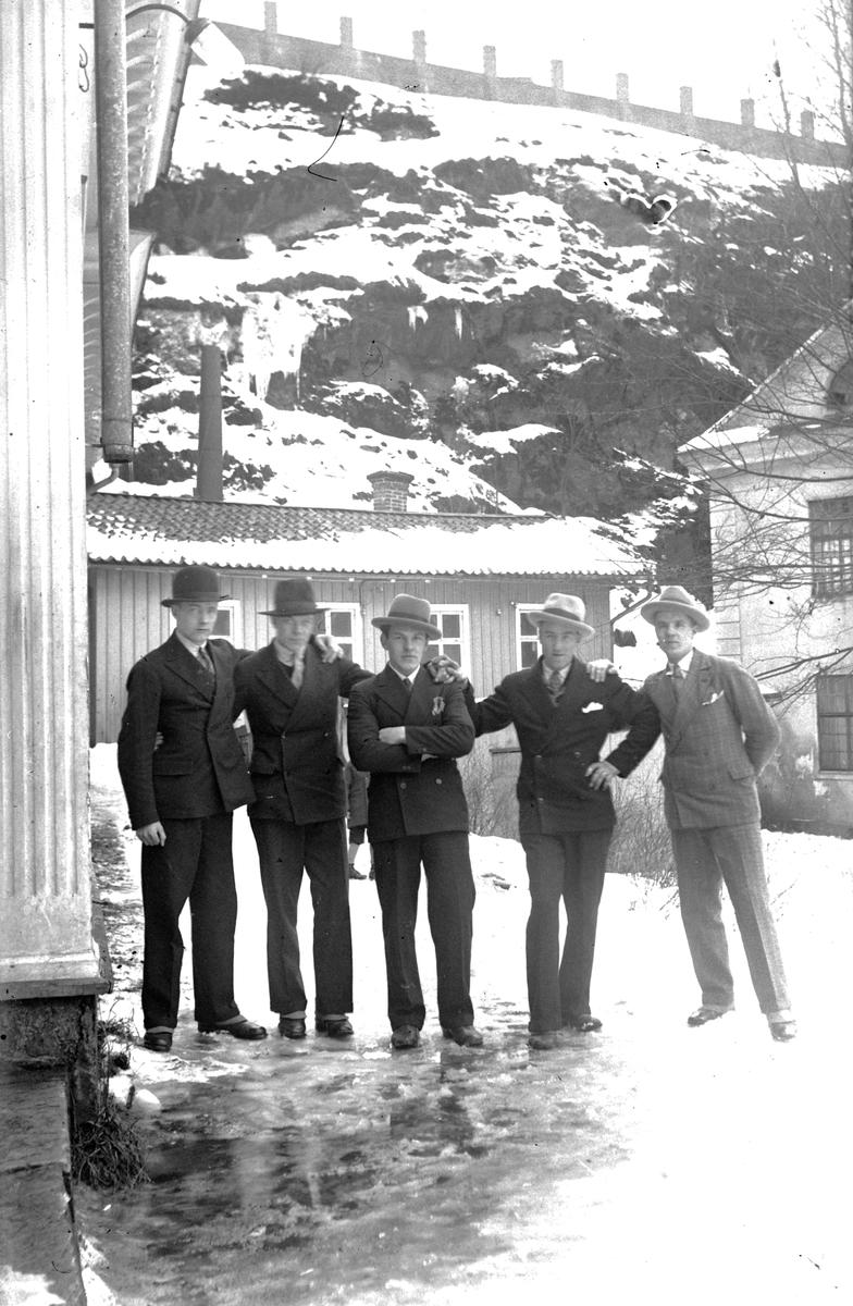Fem män står framför Storkvarn, ett lågt trähus vid Dunkehallaån i Jönköping, området brukar kallas Busahål.