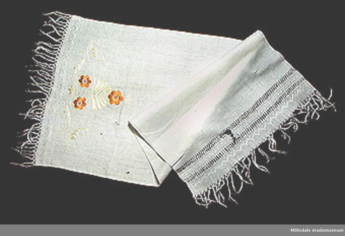 Vit paradhandduk med fransar i kortsidorna, hålsöm och broderade bårder vid ena kortsidan. Även broderat blommotiv i gult och orange silke.Tillstånd: Något trasig vid ena kortsidan.