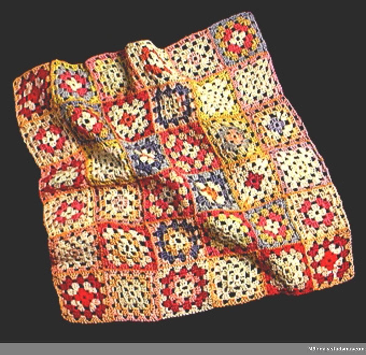 Docktäcke i form av ihopsydda virkade rutor i flera färger.