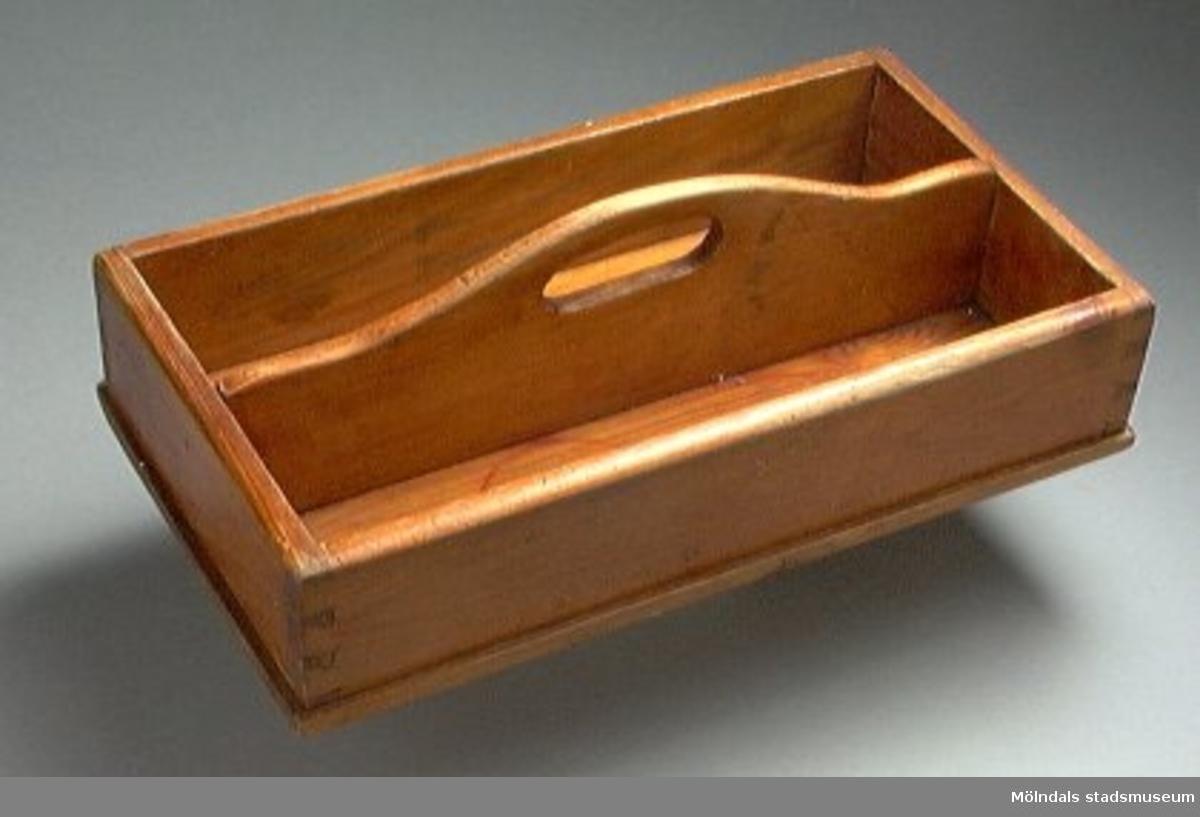 """Besticklåda av lackerat trä. Indelad i två fack. Undertill märkt med blyerts: """"A"""" (eller """"FI""""?) 8/3 39."""