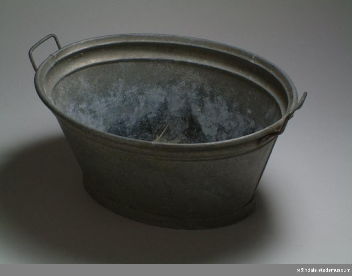Oval tvättbalja i zinkplåt, med bygelhandtag på båda sidorna.Ruth Johansson är givarens mor. Baljan användes på sommarstället i Partille.