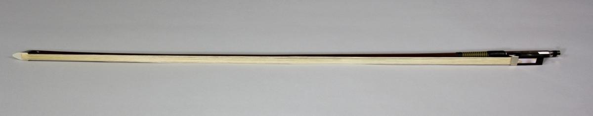 Stråke, fiolstråke, tillverkad av rödbrunt trä med ljust tagel. Vanlig modell med frosch och skruvspänning.