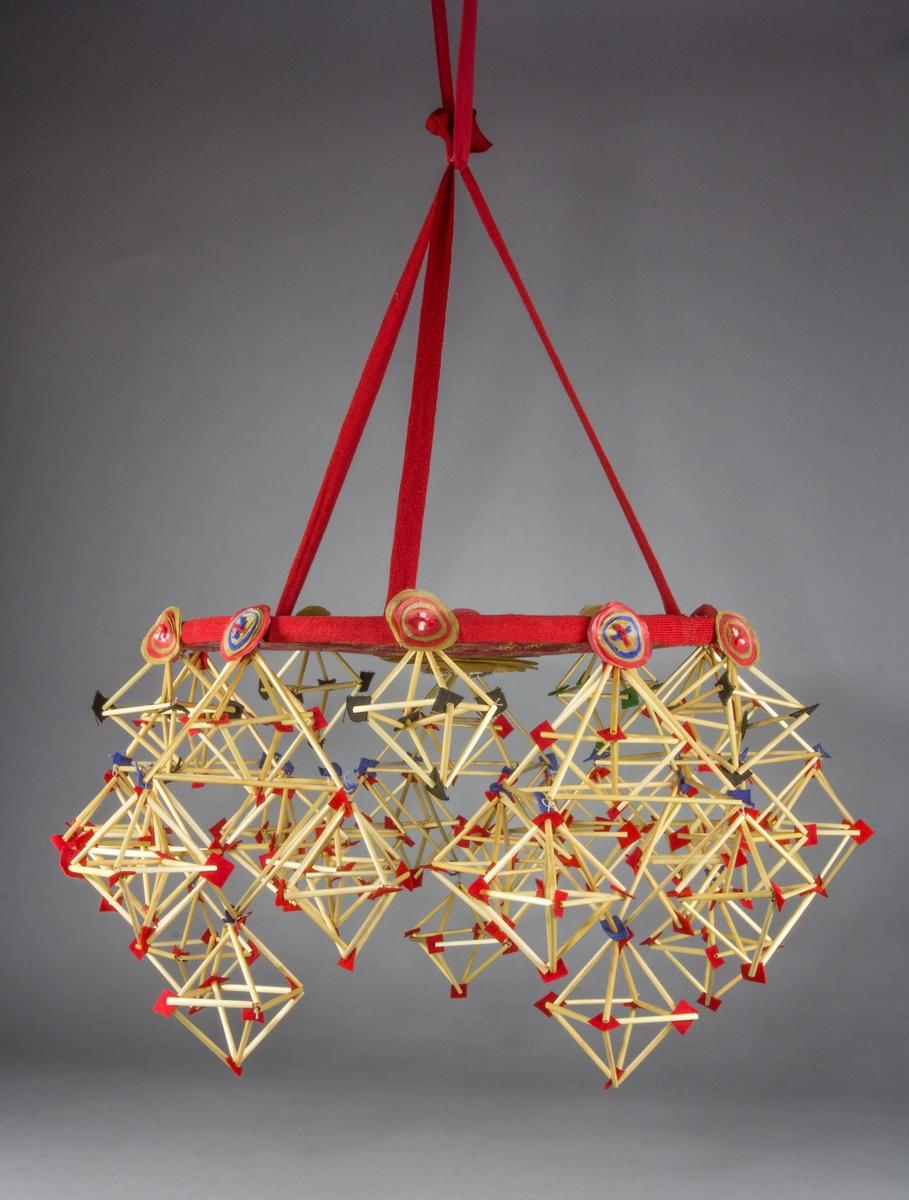 Halmkrona, gjord av tyg, band, papper, halm och garn. Den består av en skiva klädd med  rödmönstrat bomullstyg, med vågrätt plan. På kanten sitter ett maskinvävt rött band av ull. Från kanten hänger 10 fyrkanter av halmstrån, prydda med olikfärgade små filtlappar i hörnen, varannan enkel, varannan stor och försedd med egna påhängda fyrkanter. Vid varje fäste ett litet arrangemang av papperscirklar, olika färger, i mitten en garntofs. I mitten av skivan, nedåtriktat, sitter också ett arrangemang av större papperscirklar, med fransklippt papper i mitten. Upphängningsanordning av röda ullband.