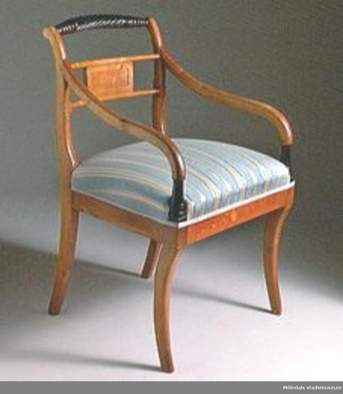 """Armlänstol av polerad björk, repformat svärtat överstycke, liten liggande rektangulär ryggbricka placerad mellan två horisontella spjälor. Sabelformade ben. Modellen kallas för """"trafalgarstol""""Omklädda och förstärkta med klossar i hörnen.Sanolikt tillverkad av samma snickare som till stolarna MM02392 - 93; Andreas Ericsson, Hassungared 1 (1790-1871)."""