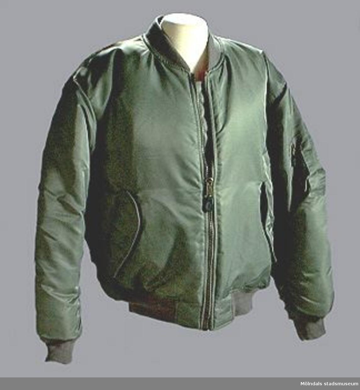Grön bomberjacka med orangefärgat foder. Ärmlängd: 505 mm. Märkt: FLY CLUB. ARCTIC STRIKE FORCE. Dragkedjor märkta: ALPHA.Tidigare sakord: bomberjacka.