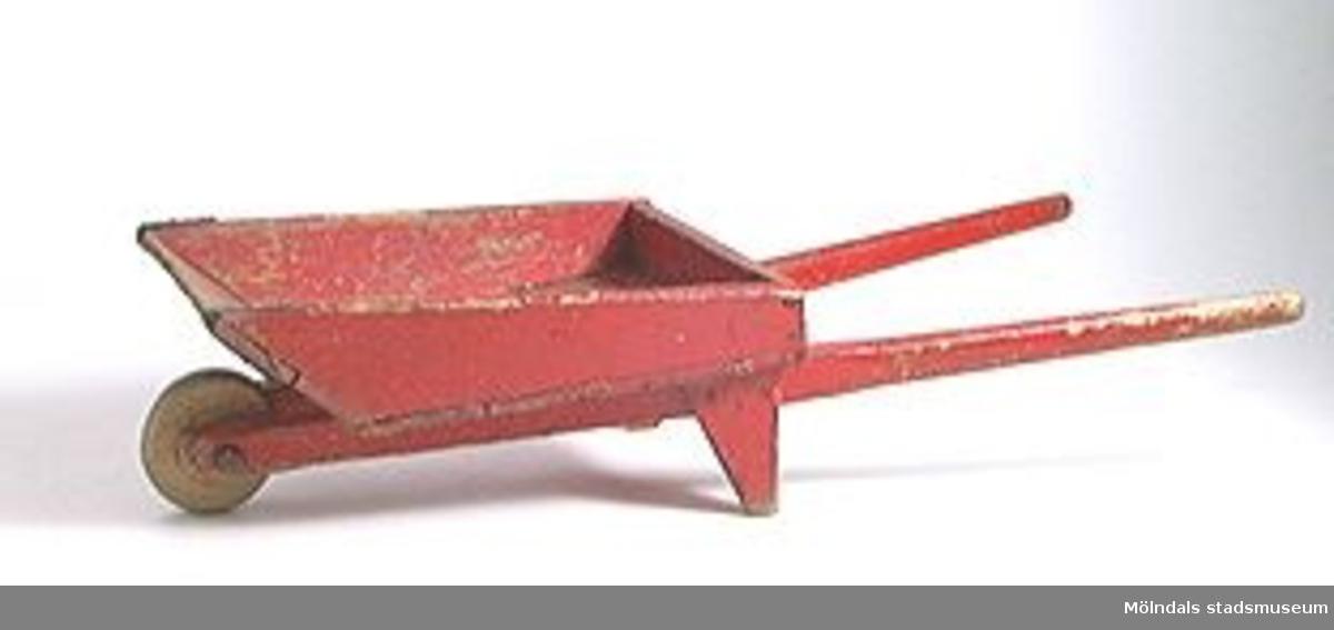 Rödmålad skottkärra i trä.Se MMF 96: 642, 6: 837.