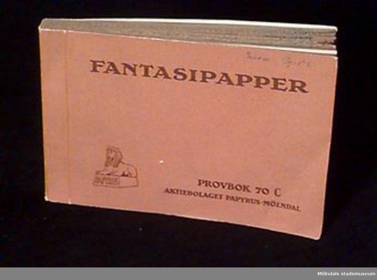 """Häftets pärm är är brun och tryckt med brun text  """"Fantasipapper"""" En handskriven anteckning i blyerts märkt i övre höger hörn lyder """" Provex 5/9-52"""". Papyrus logotype med sfinxen är märkt i nedre vänster hörn. På bokens första sida står fakta om och mått på provpapperen.Litteratur: Papyrus 1895-1945, Minnesskrift, Esseltes Göteborgsindustrier AB, Göteborg 1945."""