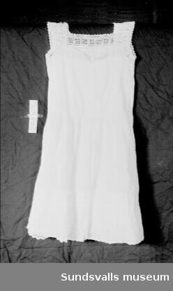 Vit hängselsärk i linne med bred virkad spets i halsen, axelband och ärmhål. Sprund i ryggen med knäppning med fyra sydda knappar. Avskuren midja. Tre breda lagda veck långt ner på kjolen.