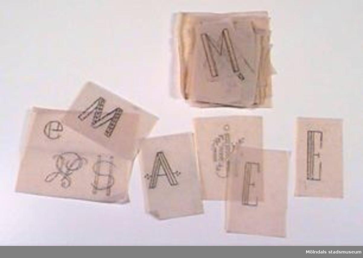 Mönster till monogram på smörpapper och tunt mönsterpapper. Det största har måtten: L 135 mm B 134 mm. Bokstäver och motiv ritade med blyerts och färgpennor. Olika initialer. Samhör med övrigt material rörande linneförråd, 02706-02722, 02727-02729.Övriga uppgifter se 02643:1.