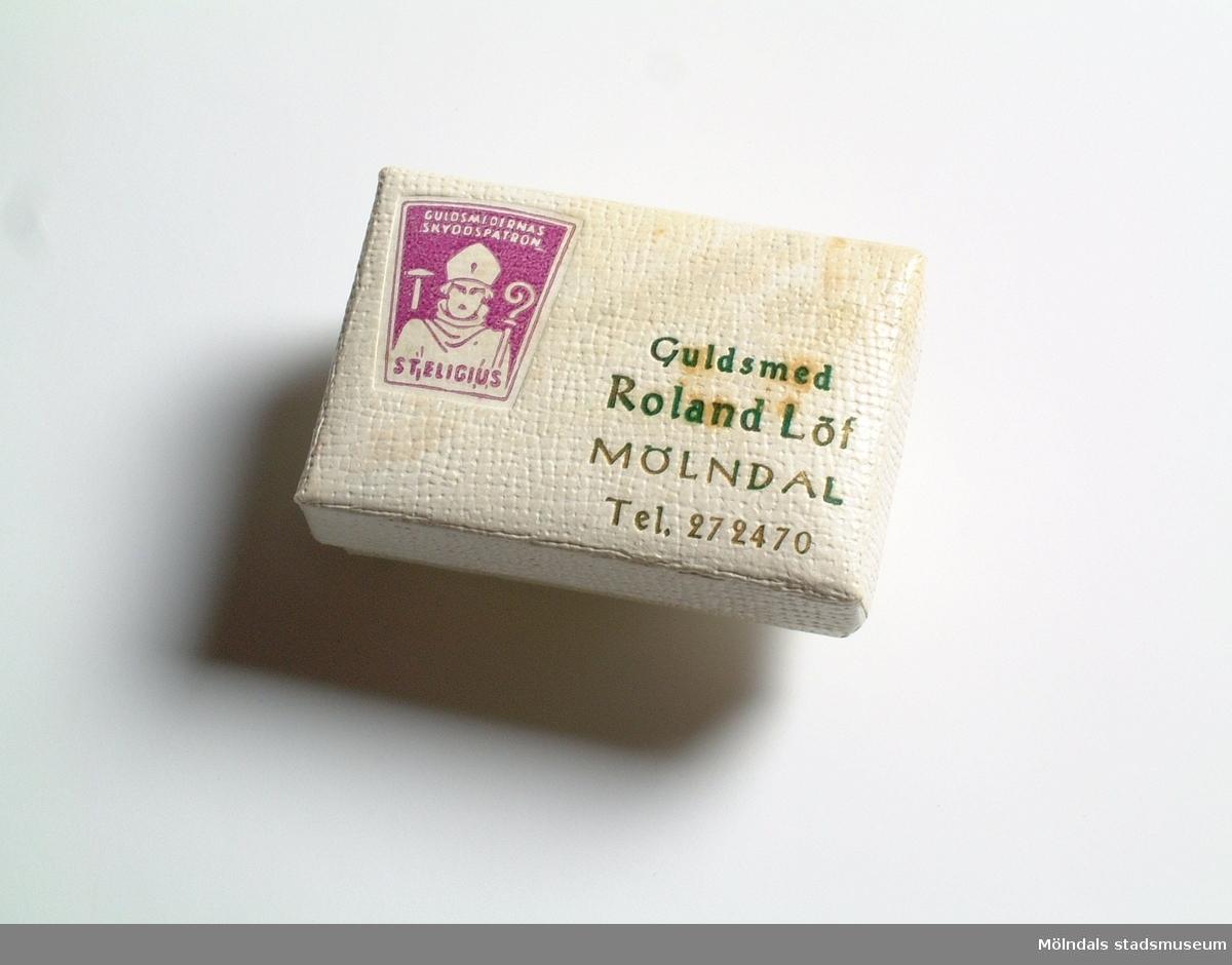 """Vit pappask med lock. Den användes till förvaring av örhängen eller halsband. På locket står tryckt """"Guldsmed Roland Löf Mölndal Tel 272470"""". Där sitter även märket St Egilius (guldsmedernas skyddshelgon). I asken ligger ljusgrön bomull.Givaren fick i födelsedagspresent silverörhängen, som låg i denna ask. Den användes sedan som förvaring till ett flertal örhängen."""