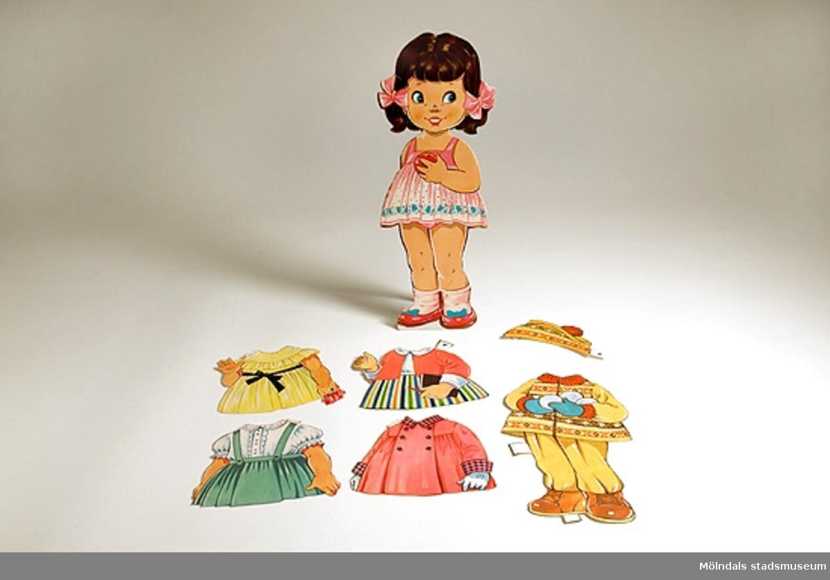 Flicka med brunt hår och rosetter i rosa underkläder.5 st. klädesplagg, 1 st. mössa.