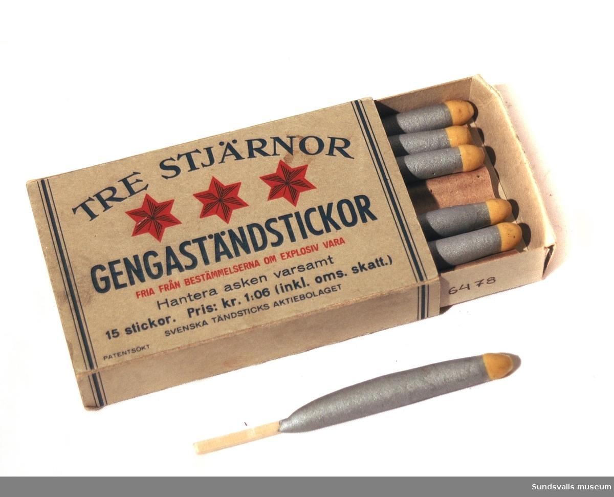 Tändsticksask bestående av två omslutande askar i grå papp innehålande 7 st tändstickor i grå höljen med gul spetts.