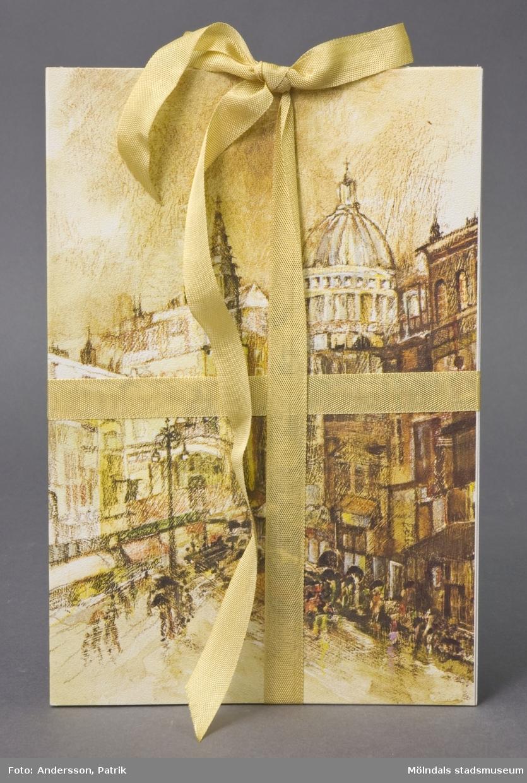 """6 st dubbla brevkort av papp med linnestruktur, ihopbundna med guldfärgat sidenband. På framsidan; målning av stadsmiljö med kupol och torg, i bruna och gröna toner. På insidan finns plats för att skriva hälsningar, gratulationer eller liknande. Text på baksidan anger: """"Rust Craft, 770770, Copyright, Printed in England"""". Motivet tryckt i England, men tillverkning har skett på Papyrus, Mölndal."""