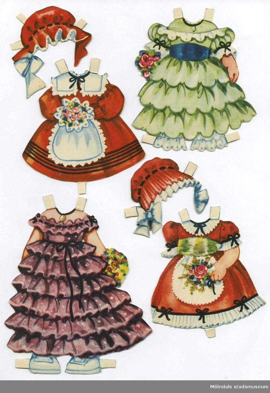 """Pappdocka med kläder från 1950-talet. Docka och kläder är märkta """"Annika 4 år"""" på baksidan - dockans namn. Dockan föreställer en liten flicka med brunt hår i flätor, iklädd underkläder med mamelucker och skor med damasker. Garderoben består av sju klänningar, långklänning, vinterkappa, nattsärk, fyra hättor samt en peruk. Docka och kläder förvaras ihop med annan pappdocka (MM 04668), i ett brunt kuvert, märkt med blyerts: """"4 år Annika"""", men är ursprungligen från """"KF Konsum - hushållens förening för lägre levnadskostnader""""."""