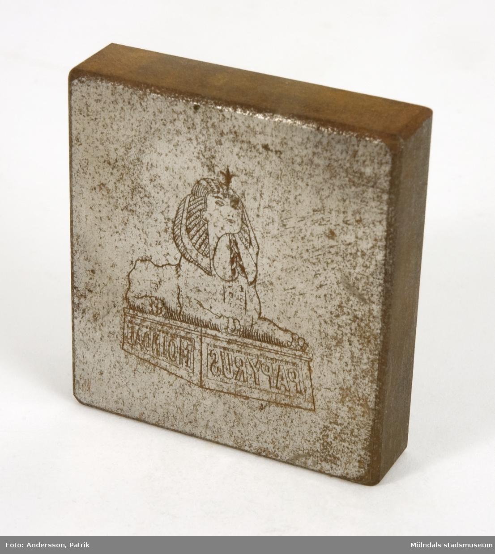 Gravyrstämpel av metall från Papyrus med företagets logotyp (sfinx på fundament) ingraverad på ena sidan. Emblemet är spegelvänt för att det skall överföras rättvänt vid tryck på papper.