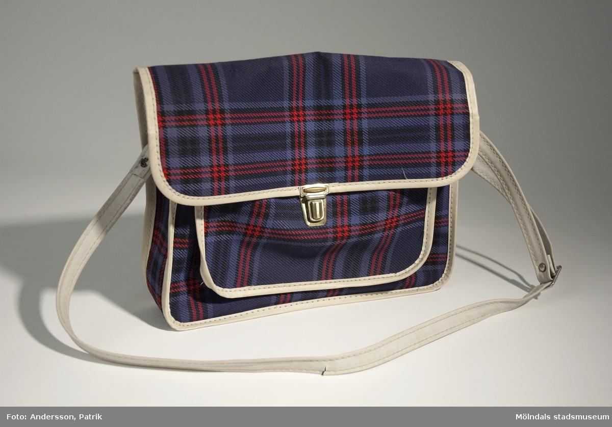 Väska med axelband. Den användes förmodligen som skolväska under 1970-talet.Väskan är blå och röd med ett rutigt mönster. Innefodret är svart och axelbandet är vitt. Den har två fack, ett större och ett mindre ytterfack. Väskan stängs med ett lock som har ett knäppe som lås.MåttBredd: 260 mm, Höjd: 205 mm, Djup: 60 mm Axelband, Längd: 833 mm.